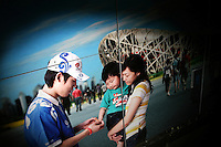 CHINA. Beijing. A picture of an Olympic volunteer helping a young child and his mother . 2008