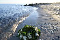 Germany, baltic sea, Burial at sea, flower wreath / DEUTSCHLAND, Ostsee, Seebestattung, Blumenkranz am Strand