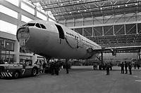 Usine de l'Aérospatiale de Saint-Martin-du-Touch, grand hall de montage. 5 février 1972. Vue en contre-plongée de l'Airbus A300 B (vue de la partie avant de l'avion) ; un tracma est accroché au train d'atterrissage avant ; techniciens autour de l'avion. Cliché pris lors du 1er déplacement tracté de l'avion encore en cours de montage.