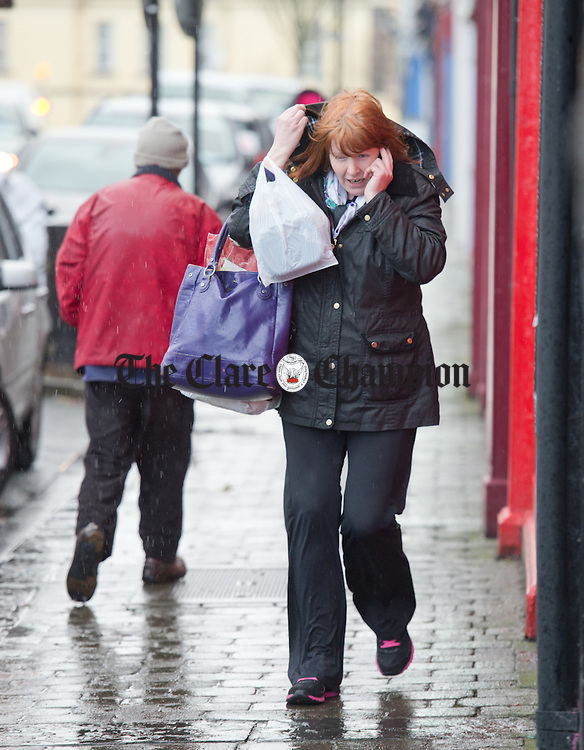 A shopper on Henry street struggles to stay dry while taking a call during a heavy downpour in Kilrush. Photograph by John Kelly.