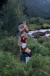 Dad & kids playing whistle game with blades of grass, Moraine Park, Rocky Mtn Nat'l Park, CO
