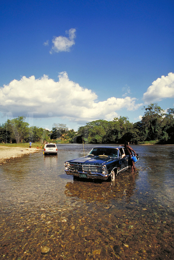 Man washing car in Macal River San Ignacio, Cayo District, Belize. San Ignacio Cayo District Belize Central America.