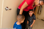 Education preschool first days of school 3 year olds female teacher with two boys one crying and sad, the other watching him