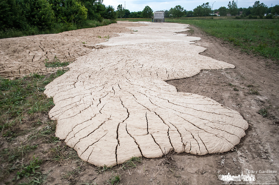 Lime sludge from a water treatment plant dries along the edge of a farm field where it was laid for use in treating the field's ability to grow a variety of crops from corn and soybeans to wheat..