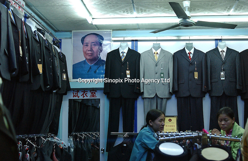 Chairman Mao sits on the wall of a clothes shop in, Changping, China..17-DEC-04