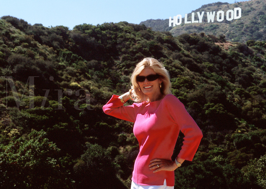 A smiling woman actress poses before the famous Hollywood Hills and signature signage. Los Angeles, California.