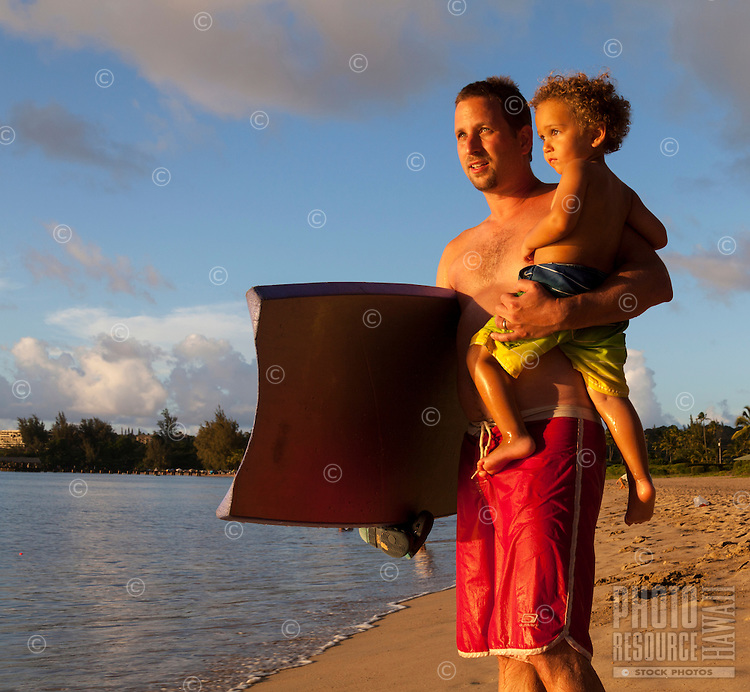 A father and son with a boogie board gaze towards sunset at Hanalei Bay, Hanalei Beach, Kaua'i.