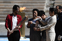 19th March 2020, Athens, Greece; The Olympic Flame, lit on Mount Olympia, is handed over officially to the  congregation from Japan, to be taken to Tokyo for the 2020 Olympic Games in July 2020. Imoto Naoko1st, an Olympian in swimming at the Olympic Games, of Atlanta 1996 passes the Tokyo Olympic flame to a container at the handover ceremony