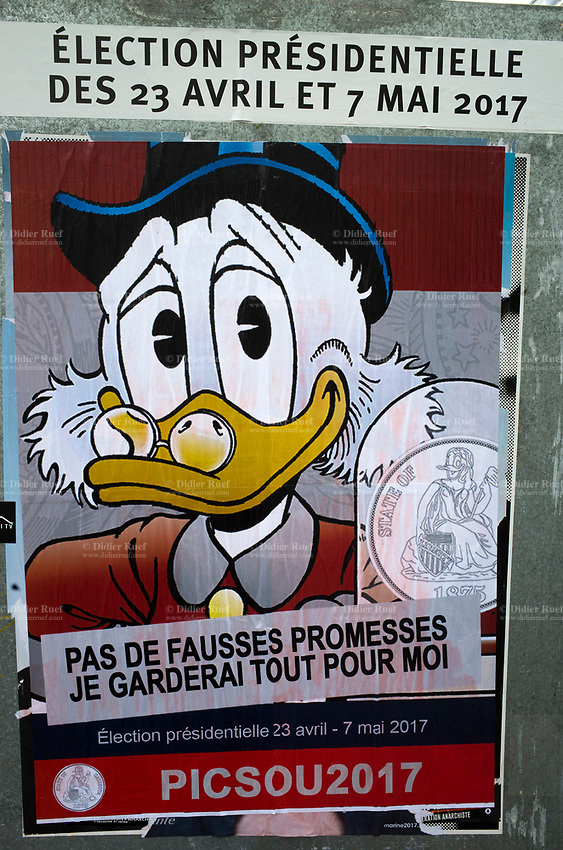 France. Ile de France. Paris. Political opponents have glued a Balthazar Picsou ( in english Scrooge McDuck) poster on an official campaign poster of a French presidential election candidate. Scrooge McDuck is a fictional character created in 1947  for The Walt Disney Company. Scrooge is an elderly Scottish anthropomorphic Pekin duck with a yellow-orange bill, legs, and feet. He typically wears a red or blue frock coat, top hat, pince-nez glasses, and spats. <br /> 22.04.17 © 2017 Didier Ruef