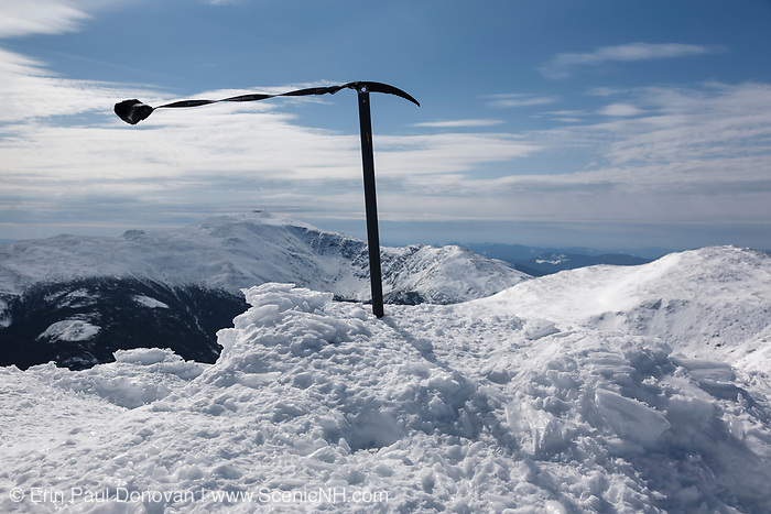 The summit of Mount Adams during the winter months in the White Mountains, New Hampshire. Mount Washington is in the distance. Strong winds cause the leash on the ice axe to blow around.