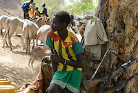 ETHIOPIA, Southern Nations, Lower Omo valley, Kangaten, village Kakuta, Nyangatom tribe, boy with rifle and machine gun Kalashnikov AK-47 for protection from cattle raids by neighbor Turkana warriors / AETHIOPIEN, Omo Tal, Kangaten, Dorf Kakuta, Nyangatom Hirtenvolk, Junge mit Gewhr und Maschinengewehr Kalaschnikow AK-47 zum Schutz vor Ueberfaellen durch Turkana Krieger