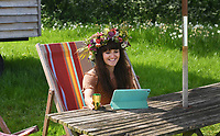 """BNPS.co.uk (01202 558833)<br /> Pic: BNPS<br /> <br /> Pictured Sunday Morning: Interactive garden day - Kate Southward dons a stunning floral head dress design by Fiona Haser Bizony for the virtual garden day in Faulkland, Somerset.<br /> <br /> Britain's biggest ever 'virtual garden party' is taking place today to help boost the nation's mental wellbeing during the lockdown.<br /> <br /> Participants in Garden Day have donned flower crowns and video-called family and friends while respecting social distancing in the sanctuary of their own gardens.<br /> <br /> The event is being supported by leading gardeners including 13 time RHS Gold medallist Chris Beardshaw.<br /> <br /> Experts are putting on floristry, food and garden tours, as well as live demonstrations on Zoom and Facebook Live.<br /> <br /> Mr Beardshaw said: """"Garden Day is the perfect opportunity for us all to get into our gardens, share our experiences virtually, and participate in a movement that sows the seeds of health, happiness and healing."""