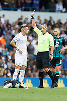 LEEDS, ENGLAND - AUGUST 31: Referee Darren Bond shows a yellow card to Kalvin Phillips of Leeds United for his foul against Yan Dhanda of Swansea City who is lying on the ground during the Sky Bet Championship match between Leeds United and Swansea City at Elland Road on August 31, 2019 in Leeds, England. (Photo by Athena Pictures/Getty Images)