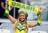 A Brazil fan kitted out in her countries colours cheers her side on before kick off
