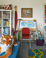 This child's bedroom features a drawing desk with a picture of a map of the world underneath a Philip Guston painting called 'Command Control' and a huge stuffed tiger.