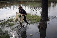 A man recovers his net which he has been using for fishing in the grounds of a flooded park. Nearly 40% of the city is below sea-level and many public areas often flood, even during the dry season.