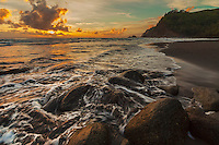 The morning sun and sky's colors are reflected on the ocean at Pololu Valley's black sand beach, Island of Hawai'i.