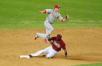 Jul. 28, 2009; Phoenix, AZ, USA; Arizona Diamondbacks base runner Justin Upton steals second base under a leaping Philadelphia Phillies infielder Chase Utley in the ninth inning at Chase Field. Mandatory Credit: Mark J. Rebilas-