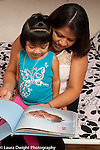 Mother reading book to 3 year old daughter at home