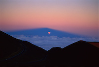 Full Moon rising in the shadow of Mauna Kea on the Earth's atmosphere, at sunset.  Mauna Kea, Hawaii.