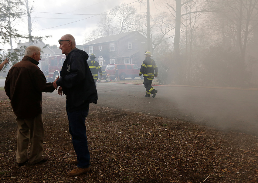 Manasquan First Aid Squad EMT Jerry Hall assists a victim through heavy smoke as Manasquan firefighters begin to battle a Pearce Ave. structure fire on Easter Sunday, April 1, 2018.