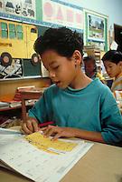 HISPANIC BOY (8) WORKING ON MATH PROBLEM AT HIS DESK IN CLASS. HISPANIC BOY (8). OAKLAND CALIFORNIA.
