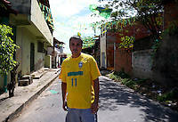 A man wearing a Brazil shirt walks down a decorated street in Fortaleza, Brazil, one of the 12 host cities of the 2014 FIFA World Cup