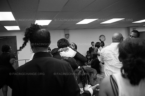 Chicago, Illinois USA<br /> August  2011<br /> <br /> Deandre Douglas mother gets hugs from friends and family members who prepare to view him for the last time. The service took place at Greater True Light M.B. Church. Deandre, 19,  was murdered on Saturday, July 10, 2011 on the 1400 block of South Millard Ave. No arrests have been made. Deandre was a member of the CYBC  boxing team on the city's West side.