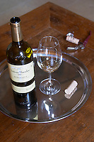 A glass of white vintage 2004 on a silver tray with the bottle and the cork and corkscrew on a wooden table top tabletop Chateau Thieuley La Sauve Majeure Entre-deux-Mers Bordeaux Gironde Aquitaine France