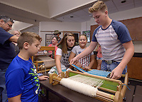 NWA Democrat-Gazette/BEN GOFF @NWABENGOFF<br /> Zack Darden (from left), 8, Katelyn Darden, Zazzi Darden, 9, and Gordon Darden, siblings from Rogers, try out different types of looms from members of the Northwest Arkansas Handweavers Guild on Sunday Oct. 2, 2016 duirng the annual Fall Festival at Hobbs State Park - Conservation Area near Rogers. The event featured a variety of family-friendly nature and old-time activities at the park's visitors center and Historic Van Winkle Hollow area.