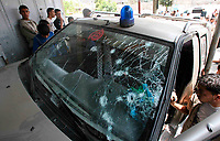 """Palestinians look at the car of senior al-Aqsa Martyrs Brigades commander Baha Abu Jarad, who was shot dead, in northern Gaza May 13, 2007. Gunmen killed a senior commander of al-Aqsa Martyrs Brigades and another member of the Fatah-linked militant group in the Gaza Strip in an attack it blamed on the rival Hamas movement.""""photo by Fady Adwan"""""""