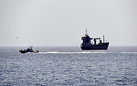 """Pictured: A Coastguard vessel (L) patrols the area near the oil spill that has reached the coast of Salamina, Greece<br /> Re: An oil spill off Salamina island's eastern coast is spreading and has become """"an environmental disaster"""" according to local authorities in Greece.<br /> The spill was caused by the sinking of the Aghia Zoni II tanker, carrying 2,200 metric tons of fuel oil and 370 metric tons of marine gas oil on Saturday, southwest of the islet of Atalanti near Psytalleia. According to reports, the coastline stretching from Kinosoura to the Selinia community has """"turned black"""" and authorities fear a new leak from the sunken ship.<br /> According to the island's mayor, Isidora Papathanasiou, the weather """"turned on Sunday afternoon and brought the oil spill to Salamina."""""""