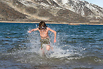 A teenage boy from the Cape Farewell Youth Expedition braves the freezing waters of the Arctic for a polar bear swim. The boy is a  student with the Cape Farewell Youth Expedition that was organized by the British Council of Canada. He is swimming in Butterfly Bay, Nunavut, Canada.