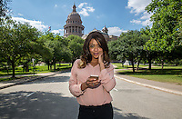 Happy african-american businesswoman using cell phone against the Texas State Capitol Dome in downtown Austin, Texas.