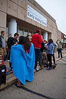 Two women shield themselves from the cold with a blanket as they wait in line at a Columbus, Ohio, early voting center on the first day of early voting in the state..