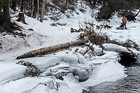 Kim Franklin passes shelf ice and open water on the trail in the Alaska Range in the Dalzell Gorge on the way to Rohn from the Rainy Pass checkpoint during Iditarod 2016.  Alaska.  March 08, 2016.  <br /> <br /> Photo by Jeff Schultz (C) 2016 ALL RIGHTS RESERVED