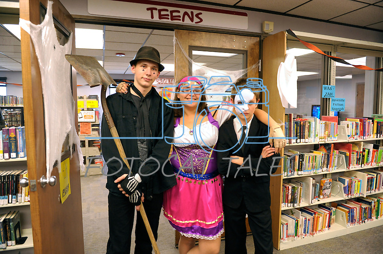 Andrew St. Geroge, 17, left, Kathryn Boatwright, 17, and Hunter Ketcham, 13, are teen volunteers at the Carson City Library Monday, Oct. 27, 2014. As part of the library's Halloween festivities the trio helped dozens of children decorate pumpkins and gourds.
