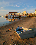 Provincetown, MA<br /> Dinghy stranded at low tide with Captain Jack's Wharf in the distance in Provincetown Harbor