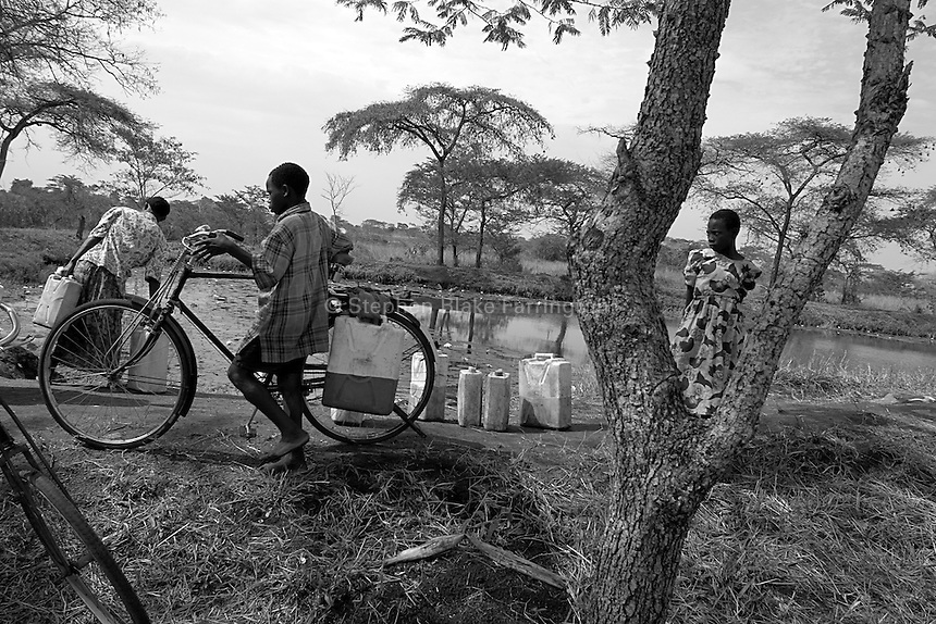 Empowering Victims of War- A scene near the water hole on the farm. Canaan Family Farm lends land to displaced people from the Northern conflict to have them learn the benefits of work and empowerment. Rwakayata, Masindi, Uganda, Africa. December 2005 © Stephen Blake Farrington