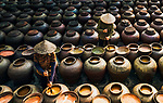Pictured: Workers stir hundreds of large ceramic pots as they spend months making a traditional soy sauce.   Arranged in rows, the containers can hold up to 50 litres of Ban Soy sauce.<br /> <br /> During the drawn out process the sauce is stirred every two days for two to six months.   Ban Yen Nhan village in the Hung Yen Province of Vietnam is famous for its traditional and distinctive method of making the sauce.   SEE OUR COPY FOR DETAILS<br /> <br /> Please byline: Nguyen Quy/Solent News<br /> <br /> © Nguyen Quy/Solent News & Photo Agency<br /> UK +44 (0) 2380 458800