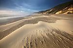 Windswept sand creates ephemeral patterns on the beach at Carl G. Washburne State Park, Oregon, USA