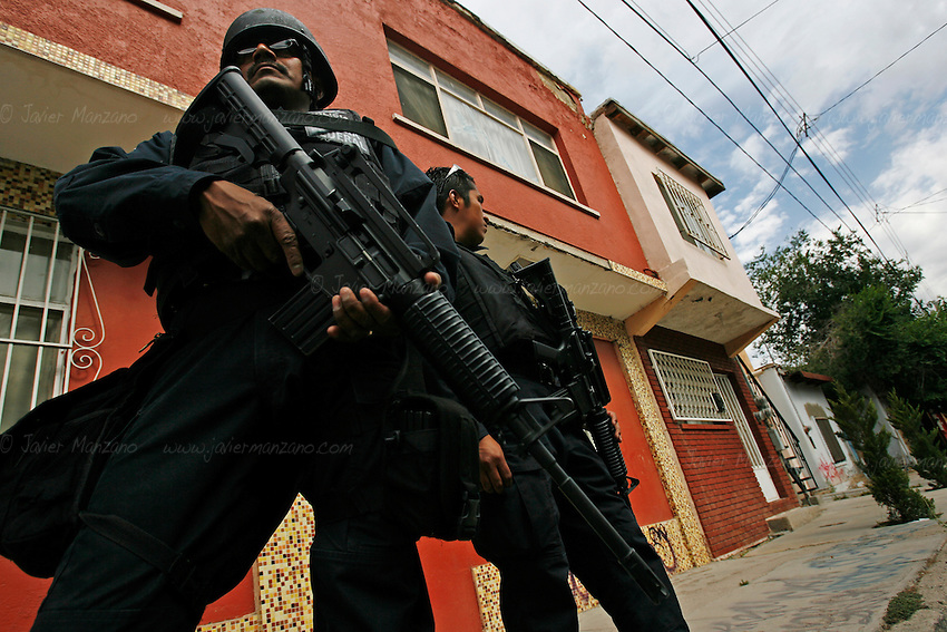 06/01/2010..Federal Police stand guard at a corner of Ciudad Juarez as CSI personnel examine a crime scene a few feet away.