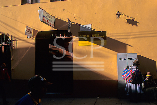 Puno, Peru. Two Quechua women outside an office with Western Union, American Express and DHL signs; shadows.