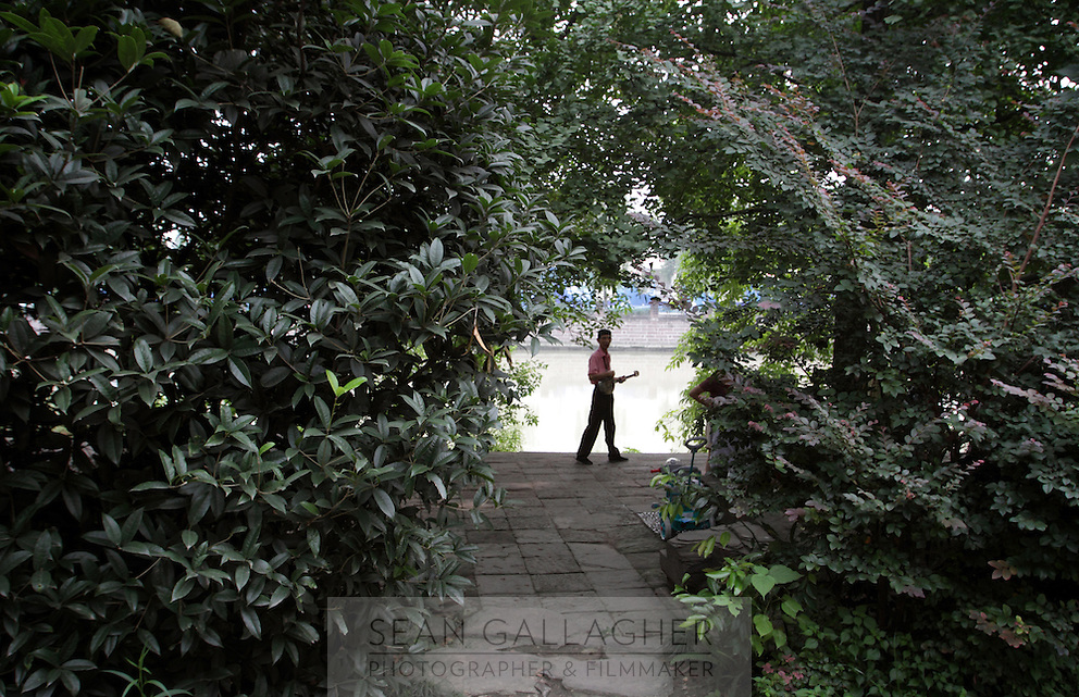 """A man with a mandolin in the """"Living Water Garden"""" in Chengdu, Sichuan Province. The garden is a park aimed at highlighting the importance of the relationship between man and water. 2010"""