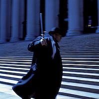 Man in suit swinging nightstick.