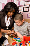 Education Preschool 4-5 year olds female teacher working with boy looking at and talking about Lego pieces colored plastic bricks vertical
