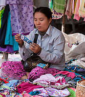 Cambodia, near Siem Reap.  Market Vendor Selling Clothing.
