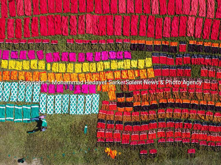 Aerial shots show rows of colourful fabric drying in the sun.  The dyed cloth is arranged on patches of grass to dry for up to six hours.<br /> <br /> Around 500 people in the village work making the hand-made made garments, which are then sent to markets both in and out of the country.  The photos were taken by Mohammad Hedayet Sarker in the village of Batik in Narayanganj, Bangladesh.  SEE OUR COPY FOR DETAILS.<br /> <br /> Please byline: Mohammad Hedayet Sarker/Solent News<br /> <br /> © Mohammad Hedayet Sarker/Solent News & Photo Agency<br /> UK +44 (0) 2380 458800
