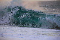 Thick shorebreak wave and foam at sunset at Ke Iki Beach on the North Shore of O'ahu.