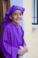 Antigua, Guatemala.  Young Boy, Dressed as a Cucurucho, Watching a Religious Procession during Holy Week, La Semana Santa